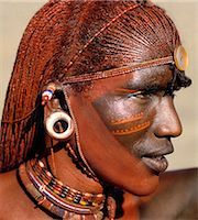 A Samburu warrior resplendent with long,braided,Ochred hair. The round ear ornaments of the warriors are fashioned from ivory. Samburu warriors are vain and proud,taking great trouble over their appearance. Ochre is a natural earth containing ferric oxide which is mixed with animal fat to the consistency of greasepaint. Stock Photo - Premium Rights-Managednull, Code: 862-03366036