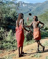 Two Samburu warriors converse,their long braids of Ochred hair distinguishing them from other members of their society. Samburu warriors are vain and proud,taking great trouble over their appearance. An ostrich feather pompom decorates the top of a spear. Stock Photo - Premium Rights-Managednull, Code: 862-03366040
