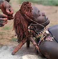 A Samburu warrior has his Ochred hair braided by a friend. A mixture of cow's urine and ashes is often rubbed into the hair first to help straighten it. The wooden headrest is used as a pillow at night. Long braids of Ochred hair distinguish warriors from other members of their society. The warriors are vain and proud,taking great trouble over their appearance. Stock Photo - Premium Rights-Managednull, Code: 862-03366042