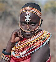 Samburu girls are given strings of beads by their fathers when they are still young. As soon as they are old enough to have lovers from the warrior age-set,they regularly receive gifts from them. Over a period of years,their necklaces can smother them up to their necks. The metal cross-like ornament hanging from the girl's headband has no religious significance. Stock Photo - Premium Rights-Managednull, Code: 862-03366047