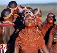 Young Samburu girls dance during a wedding celebration. By arching their backs and thrusting out their chests,they flick their beaded necklaces up and down while dancing silently to the songs of the warriors. Their bodies and necklaces have been smeared with red ochre. Stock Photo - Premium Rights-Managednull, Code: 862-03366050