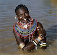 A Samburu woman resplendent in her beaded necklaces and numerous bracelets makes best use of a large rainwater pond to wash herself. Water is scarce in much of Samburuland. Stock Photo - Premium Rights-Managednull, Code: 862-03366059