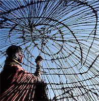 A Turkana woman makes the final ties to the dome-shaped framework of her home. In wet weather,hides will be laid on top and secured with leather thongs. Stock Photo - Premium Rights-Managednull, Code: 862-03366098