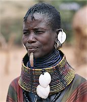 A Turkana woman wears all the finery of her tribe: brass lip plug,beaded collar decorated with bleached shells of the African land snail,leaf-like ear ornaments and metal earrings from which hang tiny rings of goat horn. Stock Photo - Premium Rights-Managednull, Code: 862-03366109
