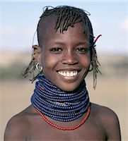 A pretty young Turkana girl has already had the flesh below her lower lip pierced in readiness for a brass ornament after her marriage. The rims of her ears have also been pierced and the holes kept open with small wooden sticks. Stock Photo - Premium Rights-Managednull, Code: 862-03366114