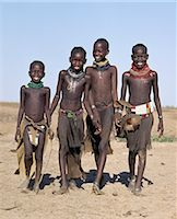 A jovial group of Turkana girls in traditional attire. Their aprons are made of goatskin,either beaded or cut into thin strips before braiding. The two girls in the middle have already had the flesh below their lower lips pierced in readiness for a brass ornament after marriage. Stock Photo - Premium Rights-Managednull, Code: 862-03366115