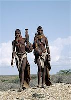 Two Turkana girls set off to fetch water from a nearby Waterhole. Their water containers are made of wood by the women of the tribe. Their 'V' shaped aprons are made of goatskin and have been edged with hundreds and hundreds of round discs fashioned out of ostrich eggshells. Stock Photo - Premium Rights-Managednull, Code: 862-03366116
