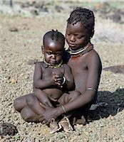 Childhood is brief in nomadic communities. From an early age,Turkana girls help their mothers with the household chores and look after their younger brothers and sisters during the day. The baby has wooden charms round her neck to ward off evil spirits. Stock Photo - Premium Rights-Managednull, Code: 862-03366121