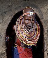 A young Maasai girl in all her finery pauses at the entrance to her mother's home. The wall and roof of the house are plastered with a mixture of cow dung and soil. Stock Photo - Premium Rights-Managednull, Code: 862-03366172