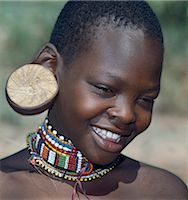 A young Maasai girl wearing a wooden plug in her pierced ear to elongate the earlobe. It has been a tradition of the Maasai for both men and women to pierce their ears and elongate their lobes for decorative purposes. Her two lower incisors have been removed - a common practice that may have resulted from an outbreak of lockjaw a long time ago. Stock Photo - Premium Rights-Managednull, Code: 862-03366174