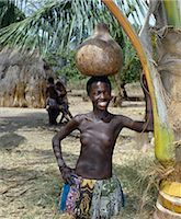A Giriama girl from Kenya's Coast Province carrying a gourd full of water on her head. Her small skirt is made from strips of printed cotton material. Stock Photo - Premium Rights-Managednull, Code: 862-03366188