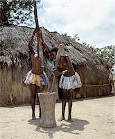 Two Giriama girls pound corn outside their home using a large wooden mortar and pestles. Their small skirts are made from strips of printed cotton material - a traditional dress of Giriama women and children. Stock Photo - Premium Rights-Managednull, Code: 862-03366189