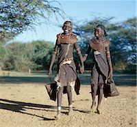 Two jovial Pokot girls set off with leather bags in search of edible berries. Pokot girls and women traditionally wore leather skirts and capes made from home-tanned goatskins. The necklaces of young girls are made from small segments of sedge grass. Stock Photo - Premium Rights-Managednull, Code: 862-03366279