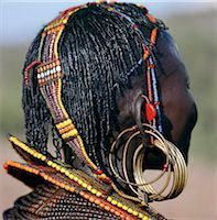 A close-up of a Pokot woman's earrings,hairstyle and beaded ornaments. Only married women wear brass earrings and glass-beaded collars. The band over her head supports the weight of her heavy earrings. Stock Photo - Premium Rights-Managednull, Code: 862-03366283