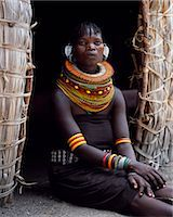 A Turkana woman,typically wearing many layers of bead necklaces and a series of hooped earrings with an pair of leaf-shaped earrrings at the front,sits in the entrance to her hut. Stock Photo - Premium Rights-Managednull, Code: 862-03366494