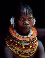 A Turkana woman sitting in the doorway of her hut. Her heavy mporro braided necklace identifies her as a married woman. Typical of her tribe,she wears many layers of bead necklaces and a beaded headband. Stock Photo - Premium Rights-Managednull, Code: 862-03366497