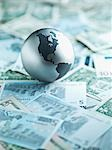 Metal globe resting on paper currency Stock Photo - Premium Royalty-Freenull, Code: 635-03372939