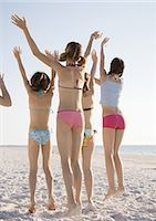 Girls jumping and waving on beach, rear view Stock Photo - Premium Royalty-Freenull, Code: 695-033