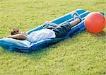 Boy sleeping on water mat on grass Stock Photo - Premium Royalty-Free, Artist: Cusp and Flirt, Code: 695-03373460