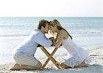 Couple kneeling on beach, head to head Stock Photo - Premium Royalty-Freenull, Code: 695-03373724