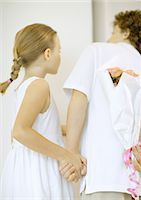 Children holding bouquet of roses behind back, looking around corner Stock Photo - Premium Royalty-Freenull, Code: 695-03373764