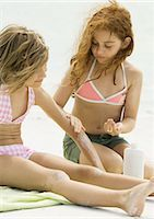 Girls sitting on beach, one applying sunscreen to the other Stock Photo - Premium Royalty-Freenull, Code: 695-03374008