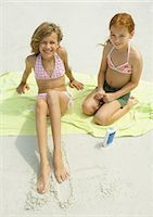 Two girls sitting on towel on beach, high angle view Stock Photo - Premium Royalty-Freenull, Code: 695-03374010