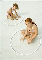 Girls sitting in rings, playing in sand on beach Stock Photo - Premium Royalty-Freenull, Code: 695-03374037