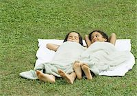 Two girls lying in grass, on a towel and covered with a towel Stock Photo - Premium Royalty-Freenull, Code: 695-03374354