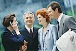 Group of business executives, one woman using cell phone Stock Photo - Premium Royalty-Freenull, Code: 695-03374464