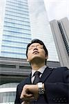 Businessman standing holding up wrist with watch, skyscraper in background Stock Photo - Premium Royalty-Free, Artist: Eyecandy Pro, Code: 695-03374742