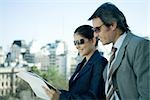 Business partners looking at documents, skyline in background Stock Photo - Premium Royalty-Freenull, Code: 695-03374837