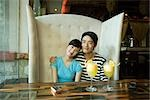 Young couple sitting in booth, cocktails on table, smiling at camera Stock Photo - Premium Royalty-Free, Artist: Kablonk! RM, Code: 695-03375073