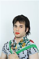 Young man wearing lipstick and scarf around neck, portrait Stock Photo - Premium Royalty-Freenull, Code: 695-03375784