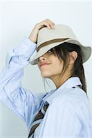 Teen girl wearing shirt, tie and hat, peeking at camera Stock Photo - Premium Royalty-Freenull, Code: 695-03375803