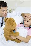 Child holding toy stethoscope to teddy bear, doctor feeling child's forehead Stock Photo - Premium Royalty-Free, Artist: Ty Milford, Code: 695-03375855