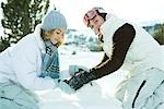 Two teenage girls crouching in snow, making snowball together, one smiling at camera