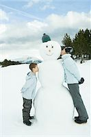 preteen kissing - Sister and brother standing, kissing snowman, side view Stock Photo - Premium Royalty-Freenull, Code: 695-03376323