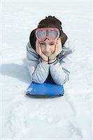 Preteen girl lying on snowboard in snow, portrait Stock Photo - Premium Royalty-Freenull, Code: 695-03376393