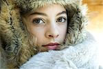 Preteen girl, wearing fur hat, wrapped in fur blanket, looking at camera, close-up portrait Stock Photo - Premium Royalty-Freenull, Code: 695-03376415