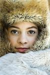 Preteen girl, wearing fur hat, wrapped in fur blanket, looking at camera, close-up portrait Stock Photo - Premium Royalty-Freenull, Code: 695-03376416