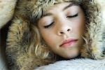 Preteen girl, wearing fur hat, wrapped in fur blanket, sleeping, close-up portrait