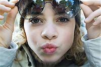 preteen kissing - Preteen girl lifting sunglasses, puckering at camera, close-up Stock Photo - Premium Royalty-Freenull, Code: 695-03376429
