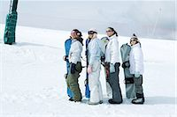 Four young snowboarders standing, lined up, looking up Stock Photo - Premium Royalty-Freenull, Code: 695-03376484
