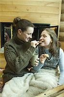sweater and fireplace - Teen girls having snack by fire place Stock Photo - Premium Royalty-Freenull, Code: 695-03376561