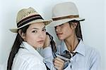 Two young female friends dressed in button down shirts, ties and hats, one holding the other's tie, looking at camera, portrait Stock Photo - Premium Royalty-Free, Artist: Ikon Images, Code: 695-03376801