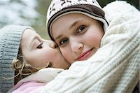 preteen kissing - Teenage girl smiling at camera, sister kissing her on cheek, portrait Stock Photo - Premium Royalty-Freenull, Code: 695-03376888