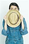 Teenage girl holding straw hat in front of face, looking away Stock Photo - Premium Royalty-Free, Artist: Hiep Vu, Code: 695-03377345