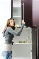 Teen girl opening pantry, looking at camera Stock Photo - Premium Royalty-Freenull, Code: 695-03377680