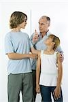 Father shaking his finger at teen son, preteen daughter watching and smiling Stock Photo - Premium Royalty-Free, Artist: Photocuisine, Code: 695-03379172